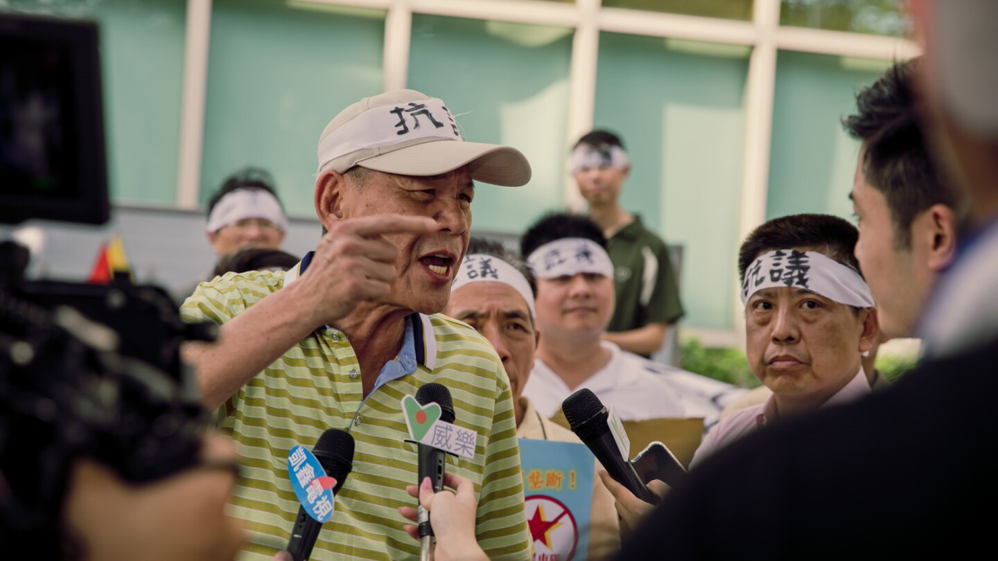 "An older Asian man talks to reporters in a still from ""A-Tien"" 