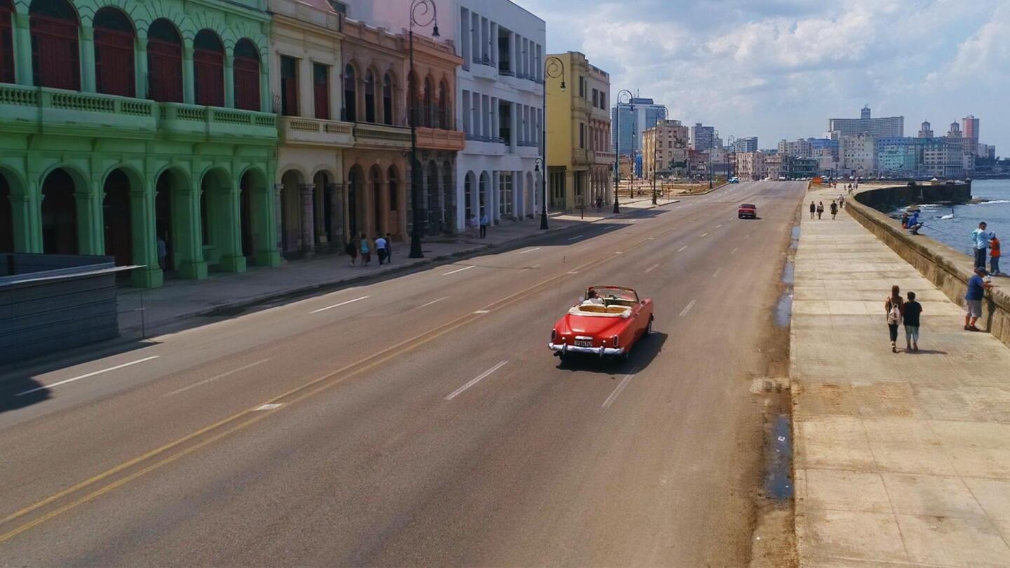"A red convertible drives along a street in Cuba next to a body of water. | ""NOVA: Cuba's Cancer Hope"""