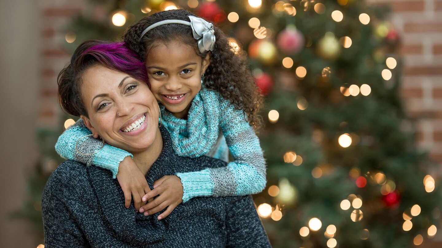 A Black woman and a small child hug each other and smile in front of an unfocused Christmas tree.istock