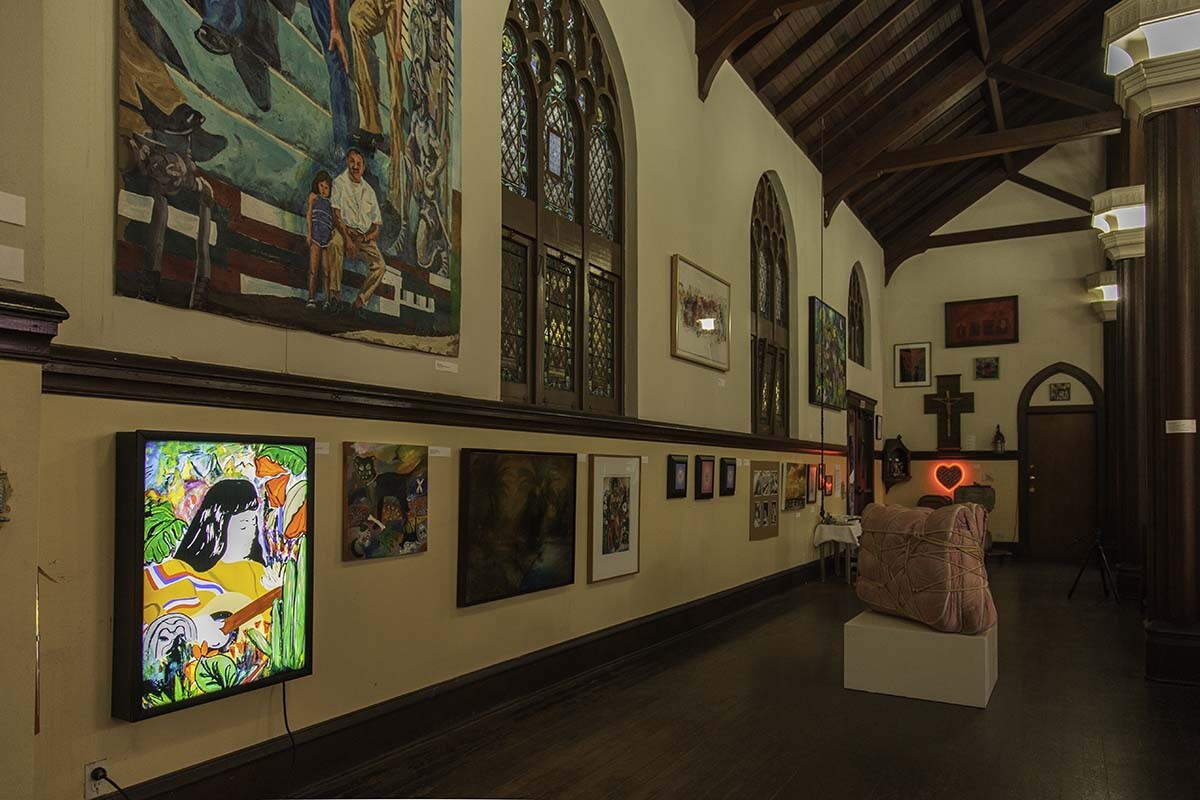 Installation view of the sanctuary. Carolyn Castaño's Other Feminist Histories ( Violeta Parra), 2015 (below) and Wayne Healy's A Mural for Ramona Gardens, 1993 (above) in the foreground.| Courtesy of Ravi GuneWardena La Raza AB s9
