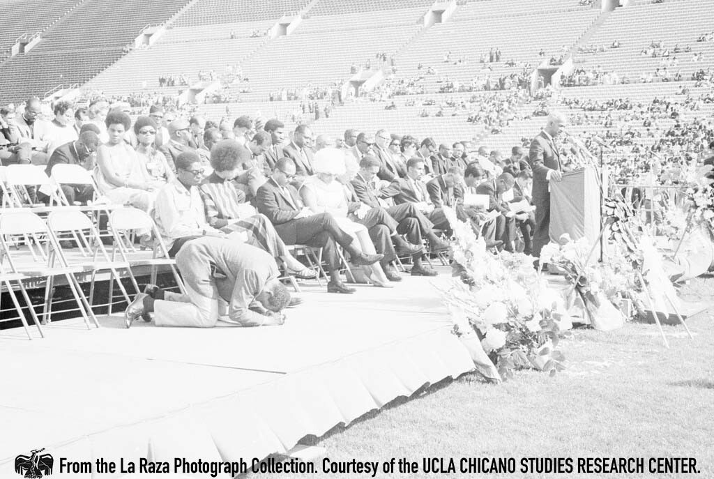 CSRC_LaRaza_B12F10C1_STAFF?__016 A man prostrates while another man speaks during a Martin Luther King Jr. Memorial in Los Angeles | La Raza photograph collection. Courtesy of UCLA Chicano Studies Research Center
