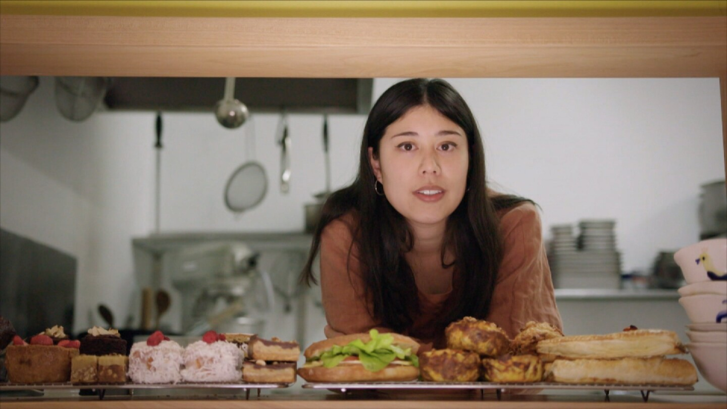 "Ruby White poses in front of desserts | Still from ""Both Worlds"""