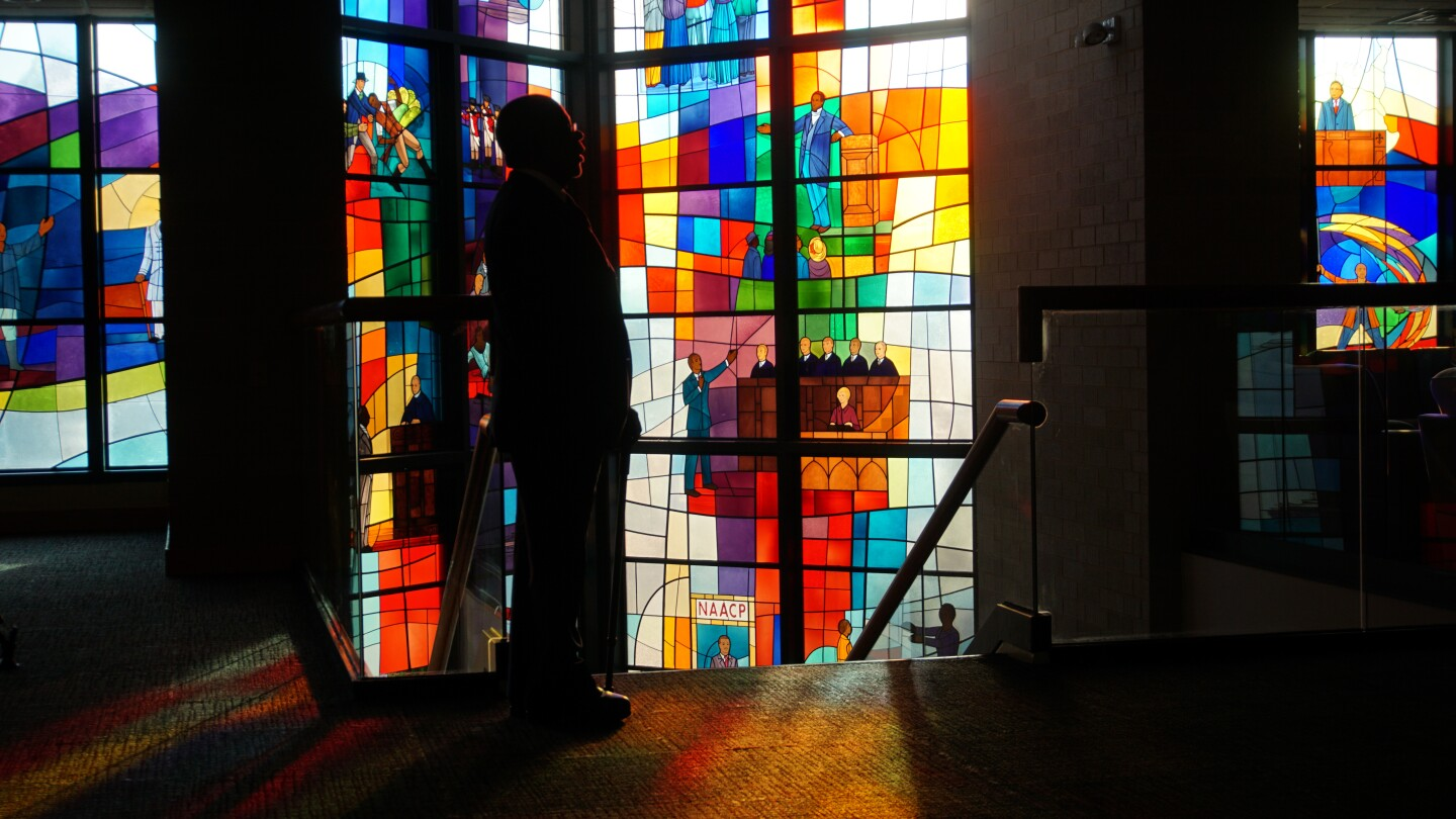 Host, Henry Louis Gates Jr. standing in front of stained glass at Trinity United Church of Christ in Chicago
