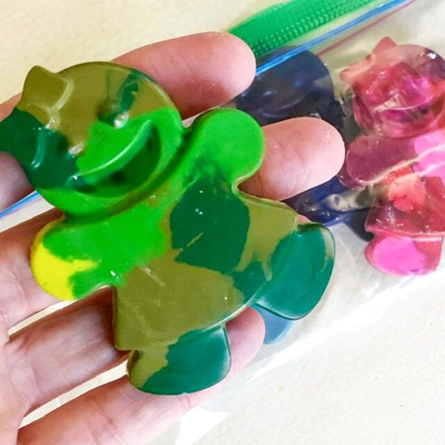 A swirled crayon in the shape of a doll with different shades of green.
