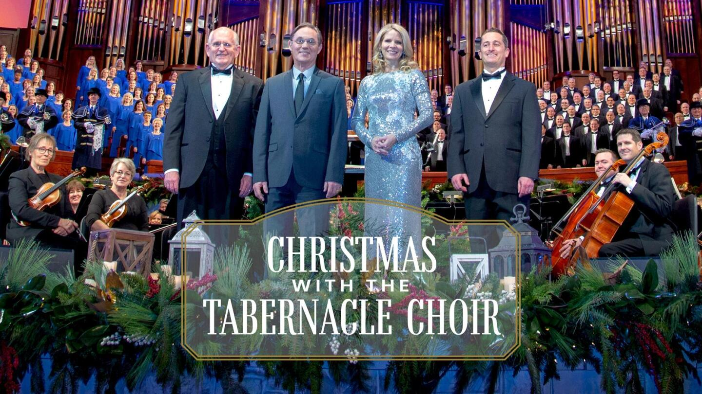 "Title card for ""Christmas with the Tabernacle Choir"" featuring four posed people and an orchestra and choir behind them."