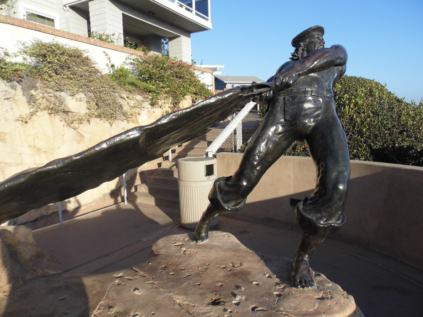 """A life-style bronze statue depicts a """"hide-drogher"""" tossing his cowhide."""