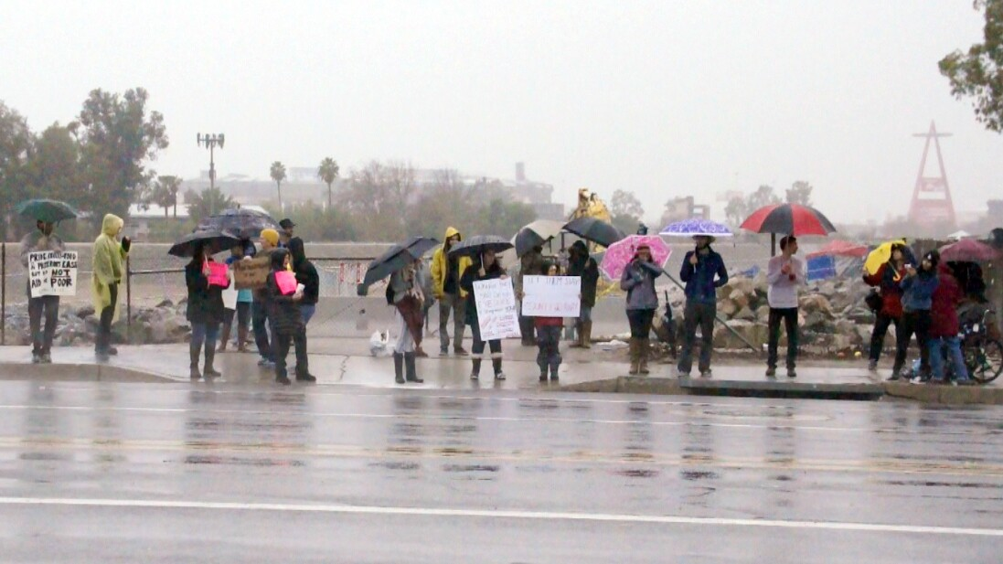 Demonstrators hold signs along Chapman Ave. next to the Santa Ana River   photo by Nick Gerda/Voice of OC