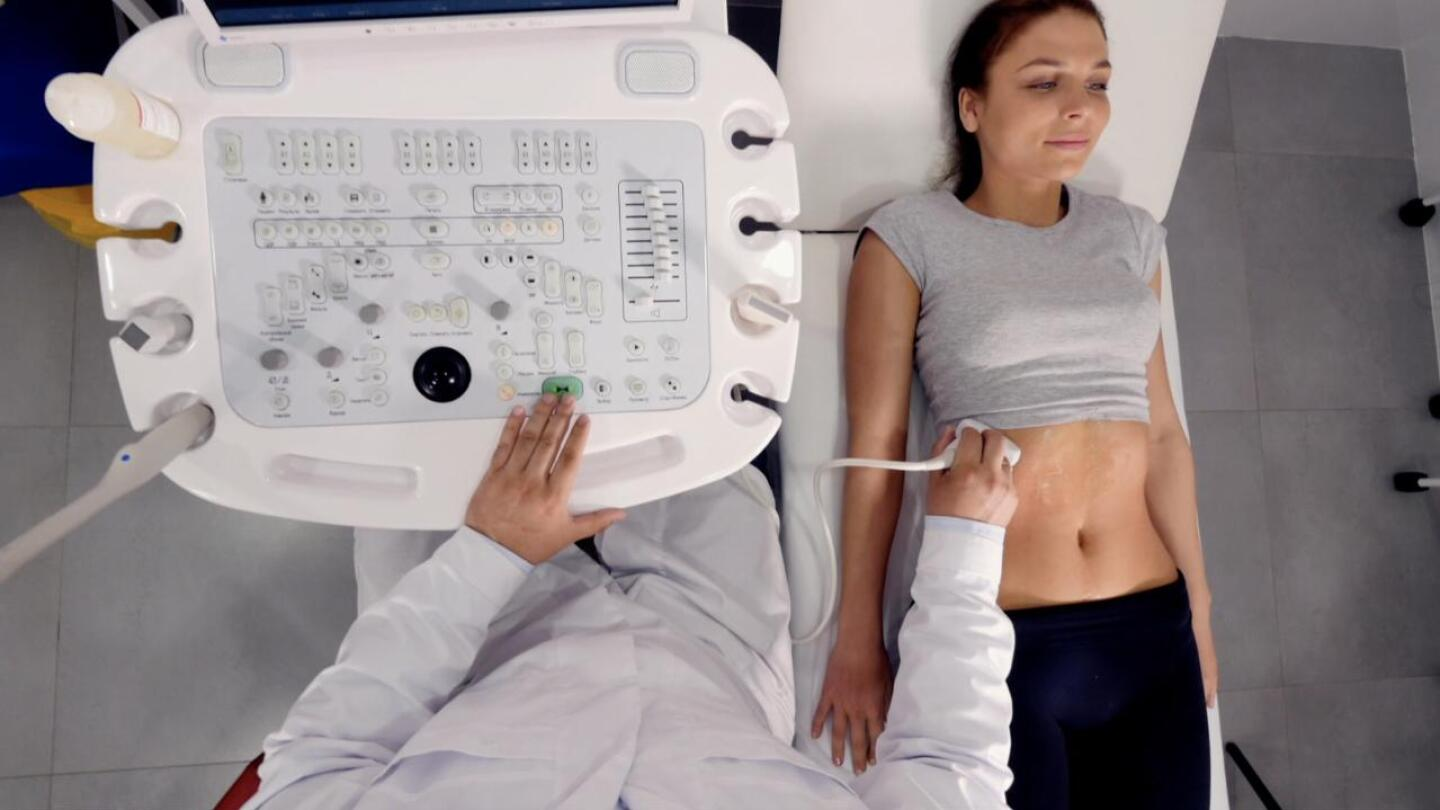 A woman's abdomen being examined with an ultrasound.
