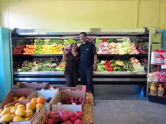 Storeowners Kulwant and Balwinder Songu in front of their new produce case at Yash La Casa Market.