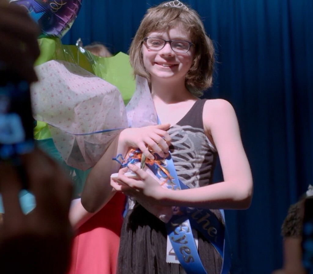 """Ren McCarthy holds a bouquet of flowers and smiles on a stage.   """"America ReFramed: Little Miss Westie"""""""