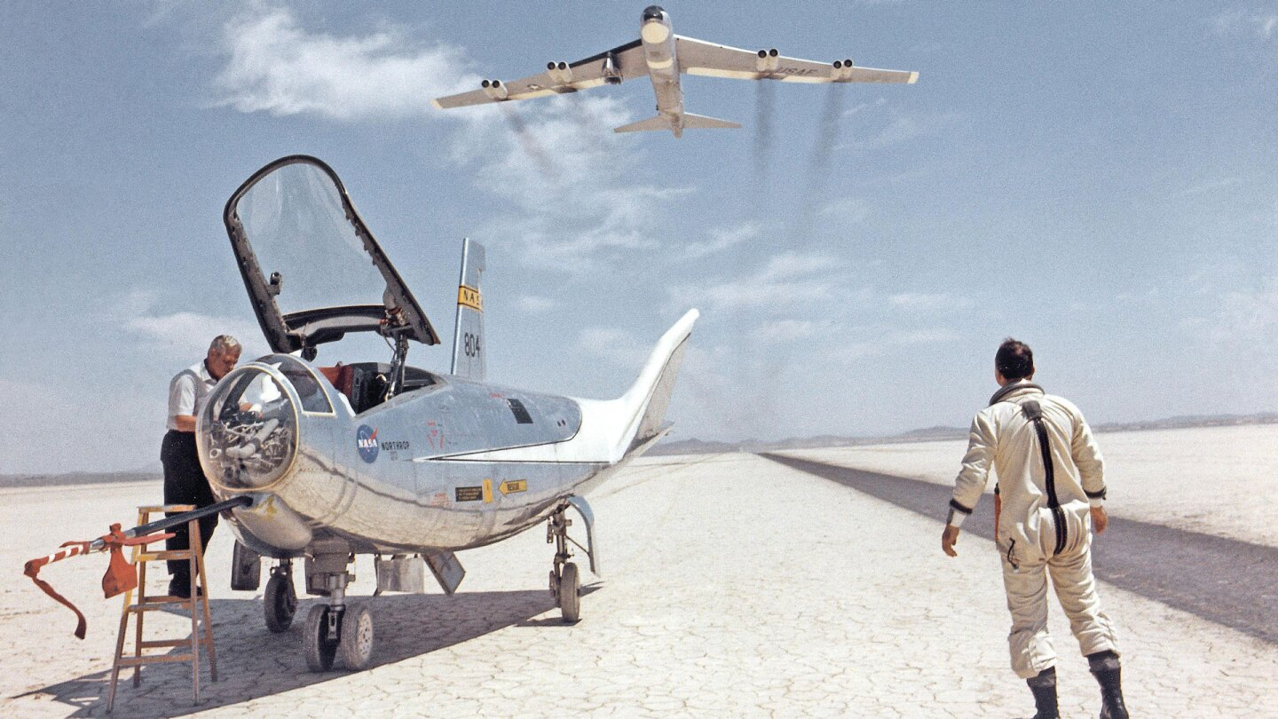 HL-10 on dry lakebed with B-52 flyby, c. 1966 | Courtesy NASA
