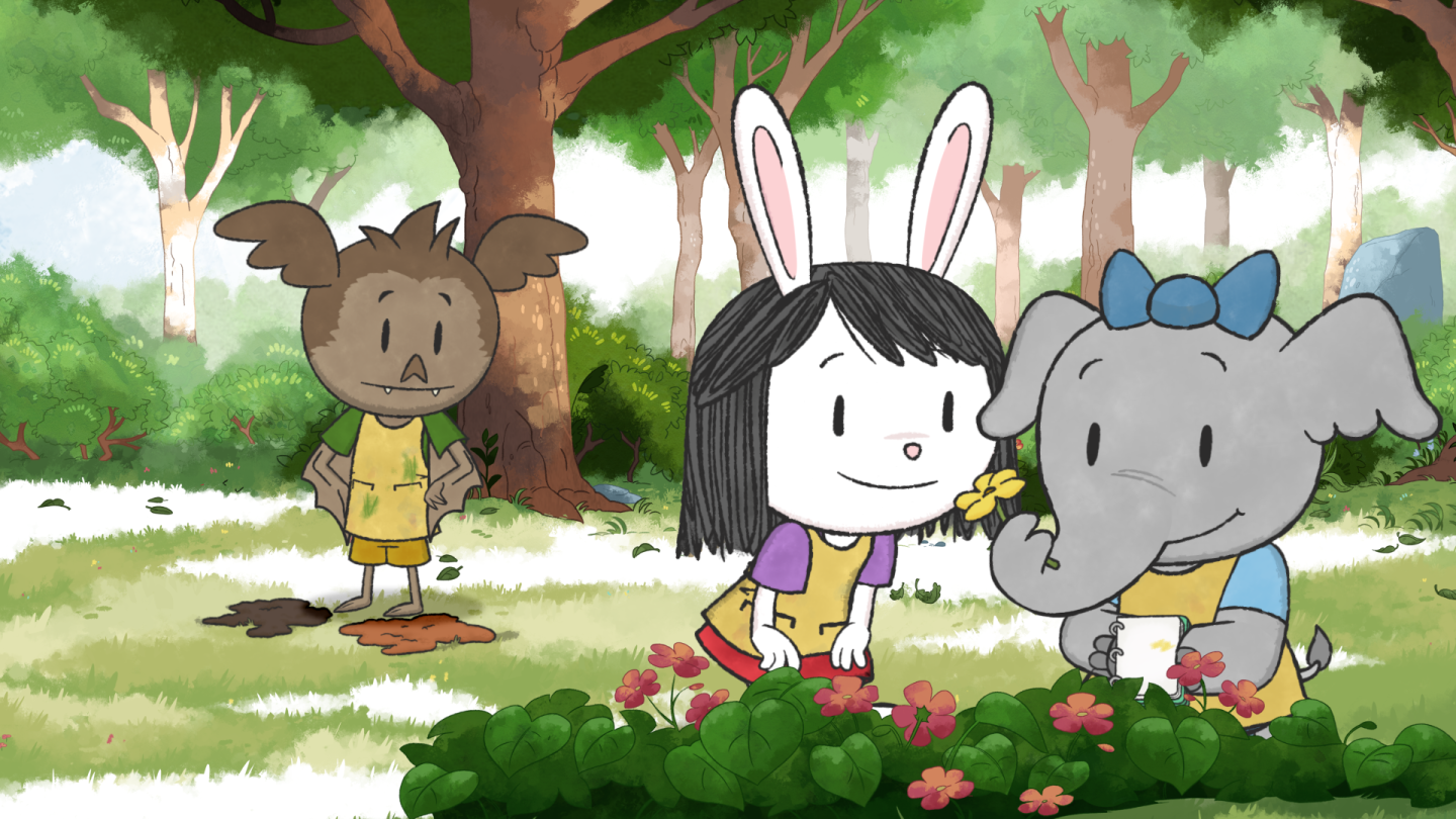 "Cartoon from ""Elinor Wonders Why"" featuring three childlike animals (a bat, rabbit and elephant) in the forest. The rabbit and elephant are smelling flowers."