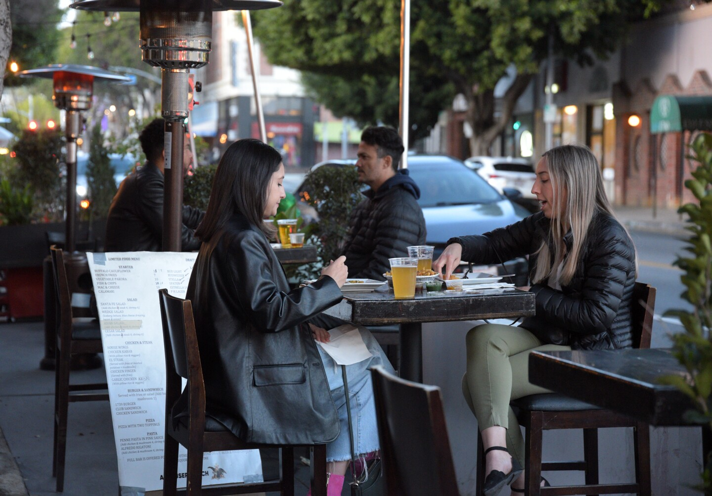 Diners eat dinner at a restaurant's outdoor tables on March 17, 2021 in Los Angeles, California.