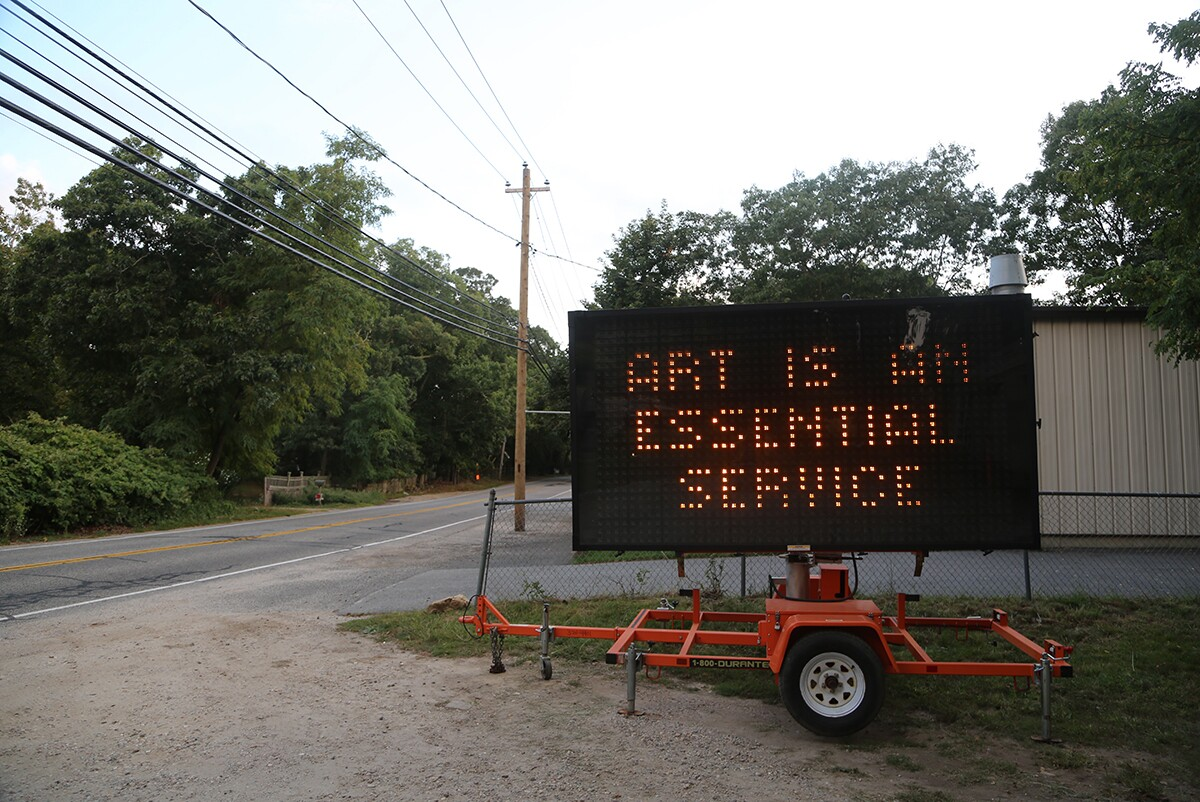 """A highway sign that says """"Artists are Essential Workers"""" outside the Fireplace Project placed by Warren Neidich 