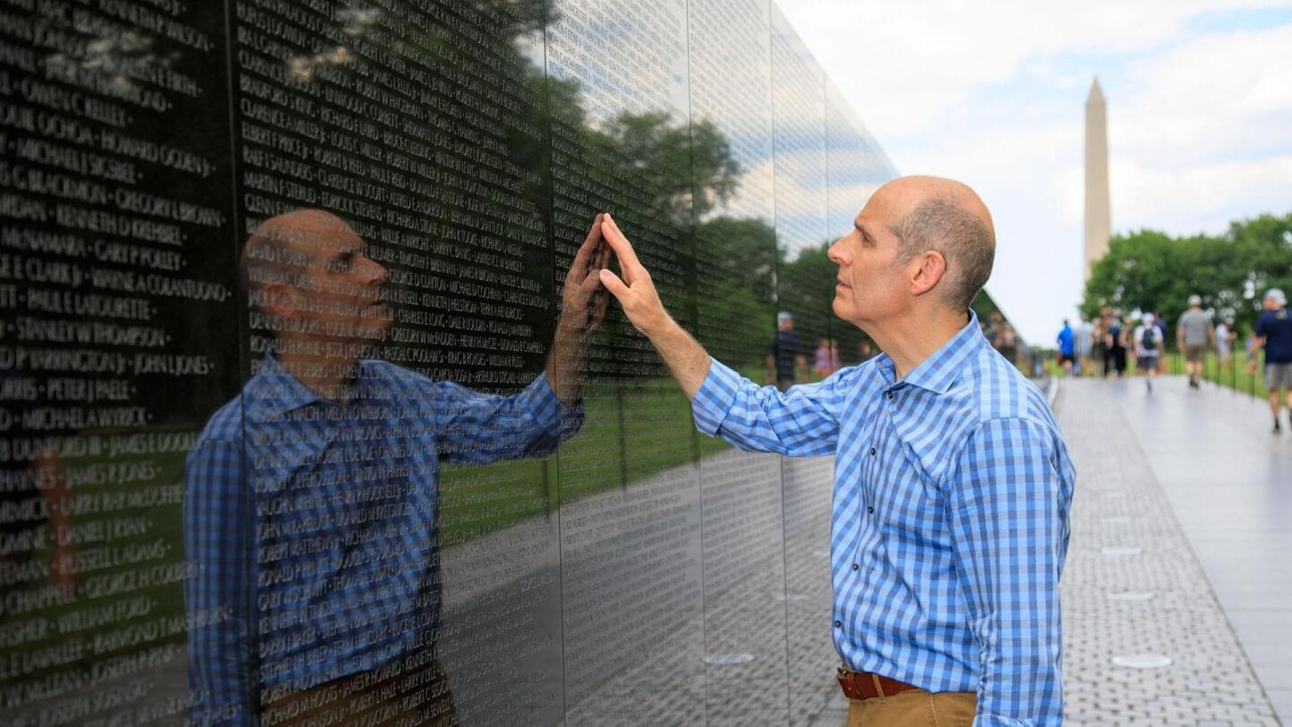 Host Geoffrey Baer places his hand on the Vietnam Veteran's Memorial as he reads the etched names in Washington D.C.