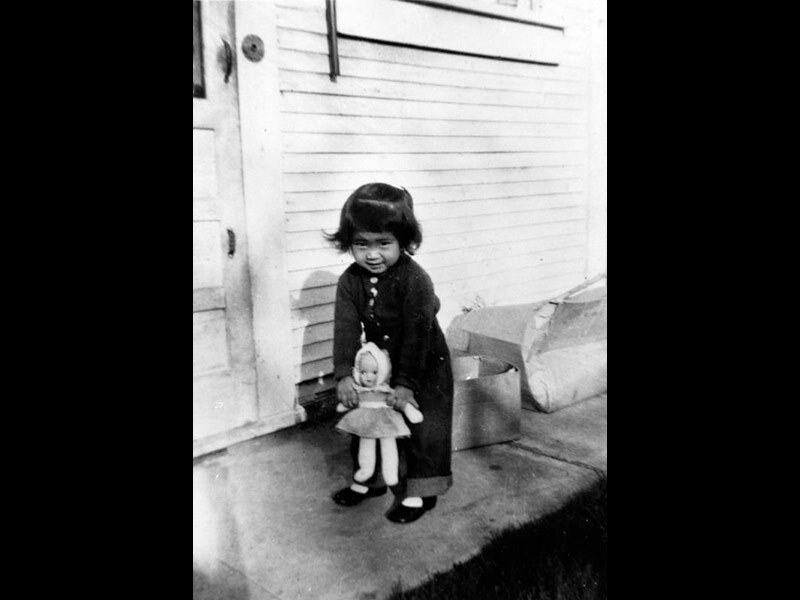 Black and white photo of a little girl standing holding a doll.