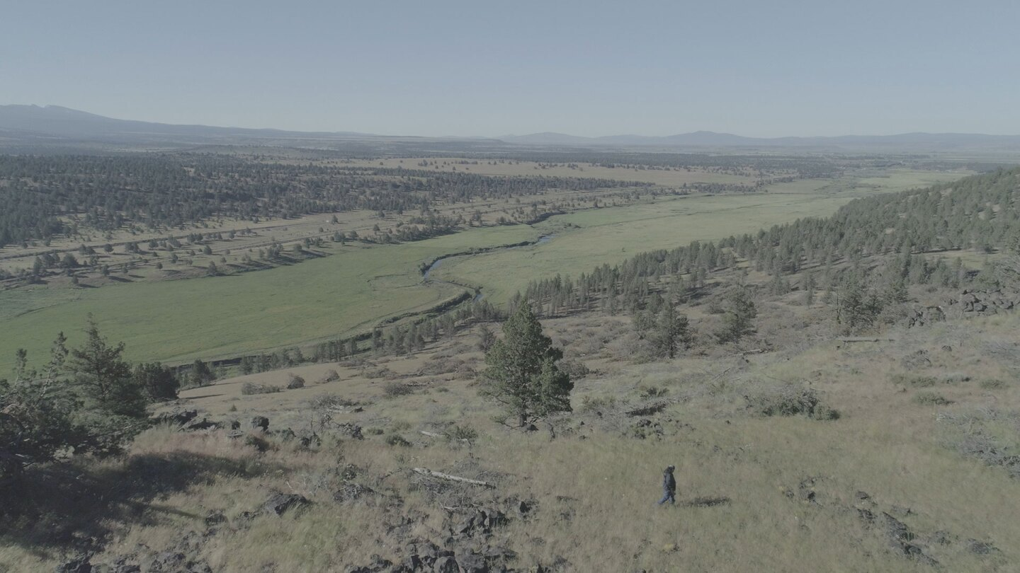 """Ray Alvarez walking through open land along the Pit River. 