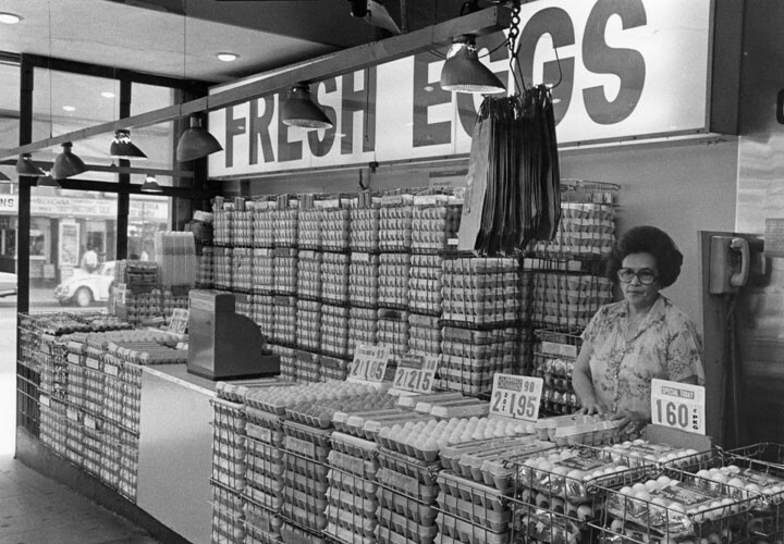A lady clerk stands behind stacks and stacks of cartons of eggs at an end booth at Grand Central Market | Courtesy of William Reagh Collection at the Los Angeles Public Library