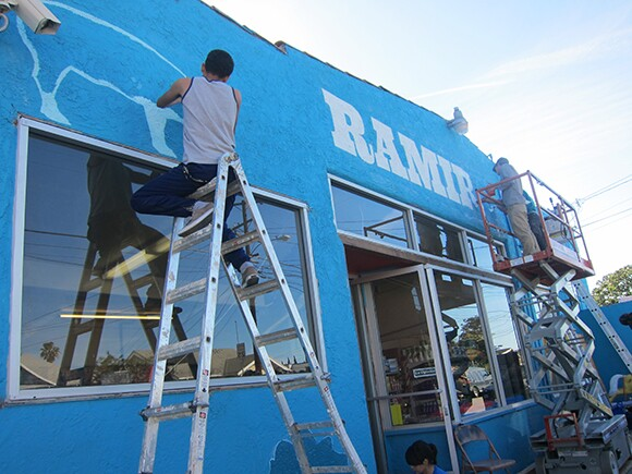 School of Communications, New Media + Technology (CNMT) at Roosevelt High School student Diego Garcia painting the exterior of Ramirez Meat Market, the 2nd transformed Proyecto MercadoFRESCO East L.A market.