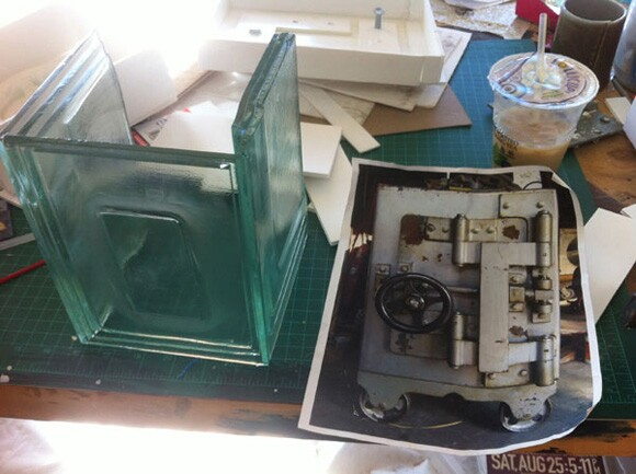 Test pieces for Liz Glynn's glass copy of a Diebold safe in her studio. The original safe is pictured in the photocopy at right | Photo: Sharon Mizota.