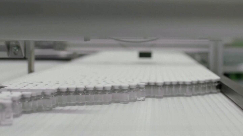 Vials of vaccines on a conveyor belt.