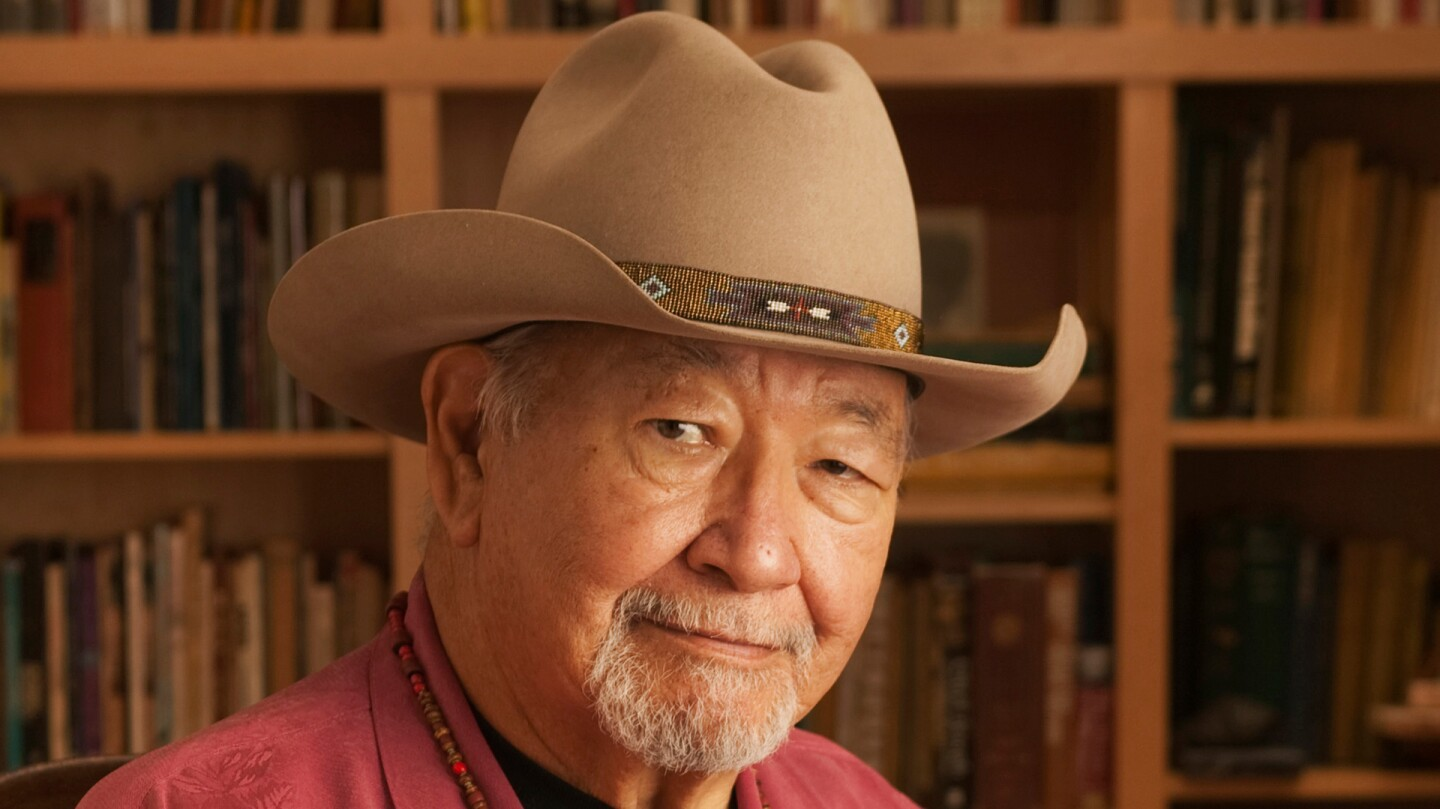 Dr. N Scott Momaday holding his literary work, The Way To Rainy Mountain