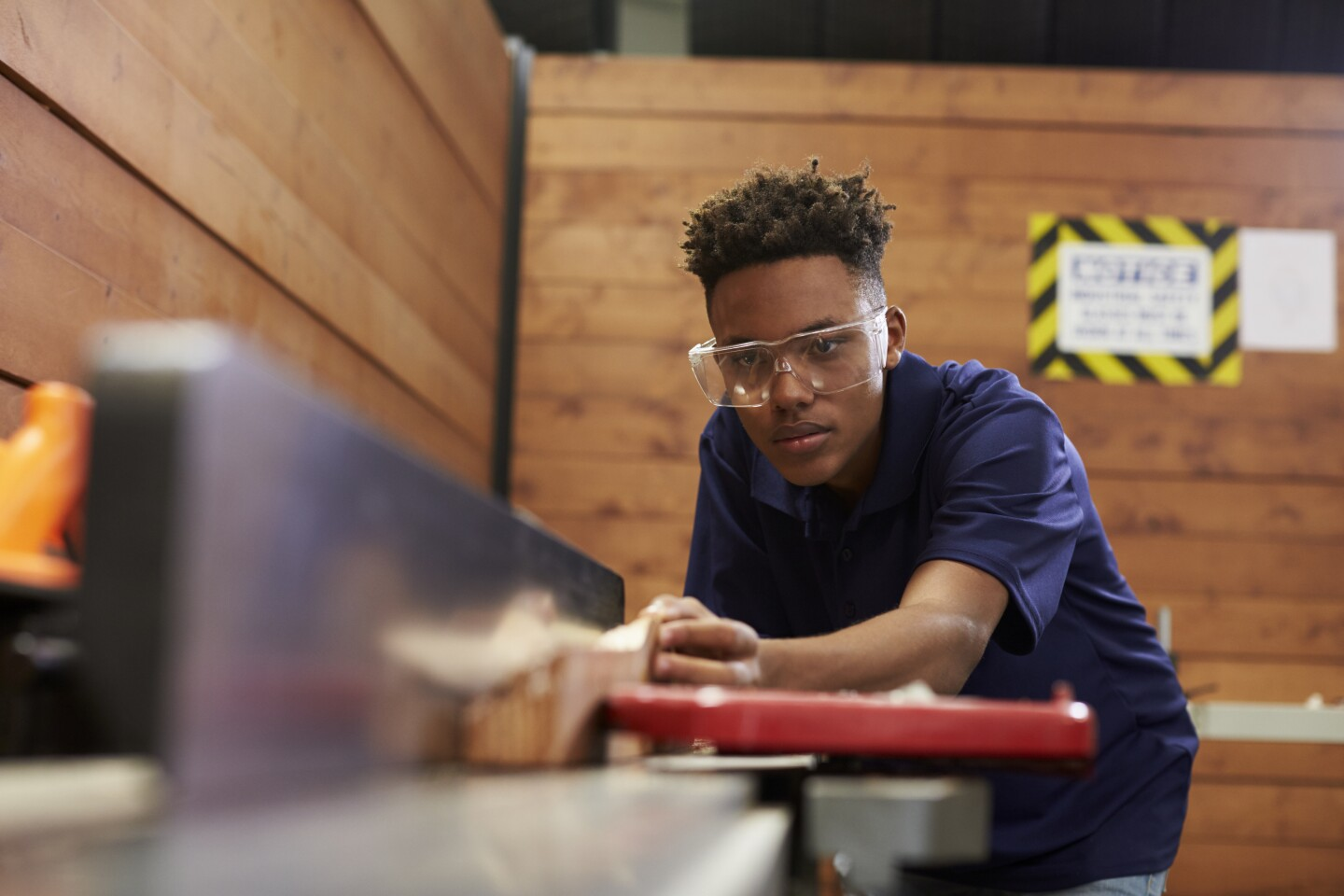 A carpenter uses a plane in a woodworking woodshop.