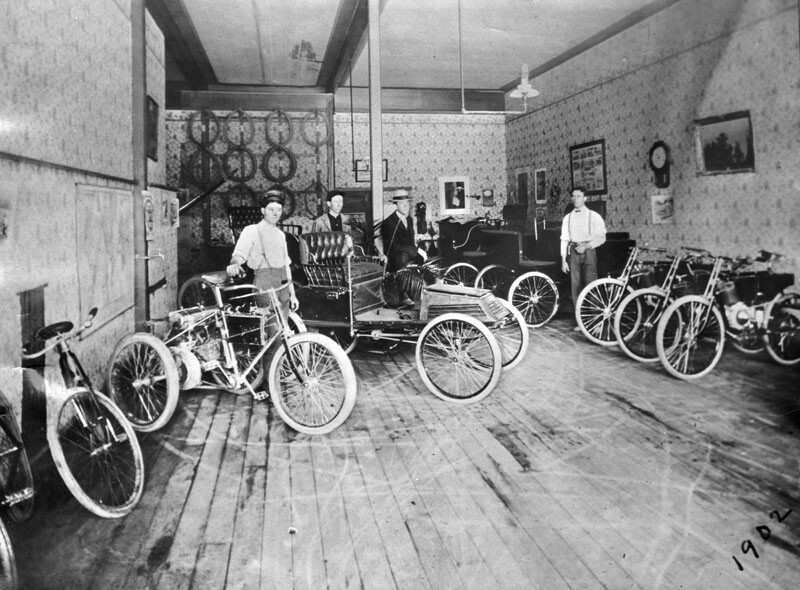 "Employees stand by early motorcycles and ""horseless carriages"" parked on a wooden floor in one of Ralph Hamlin's shops. The photo's original caption reads: ""This was Hamlin's salesroom in 1902, located at 1837 South Main Street."