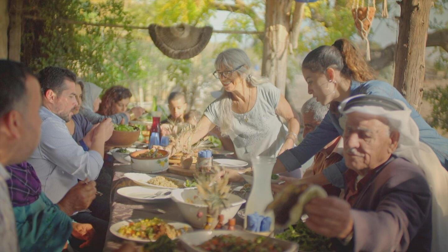 An Israeli family share a meal together on a long table.
