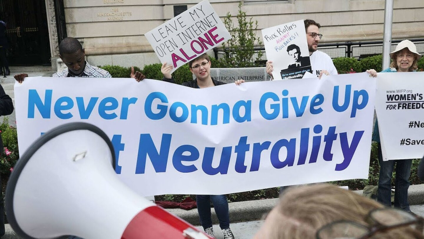 "Demonstrators holding a sign saying ""Never Gonna Give Up Net Neutrality."" 