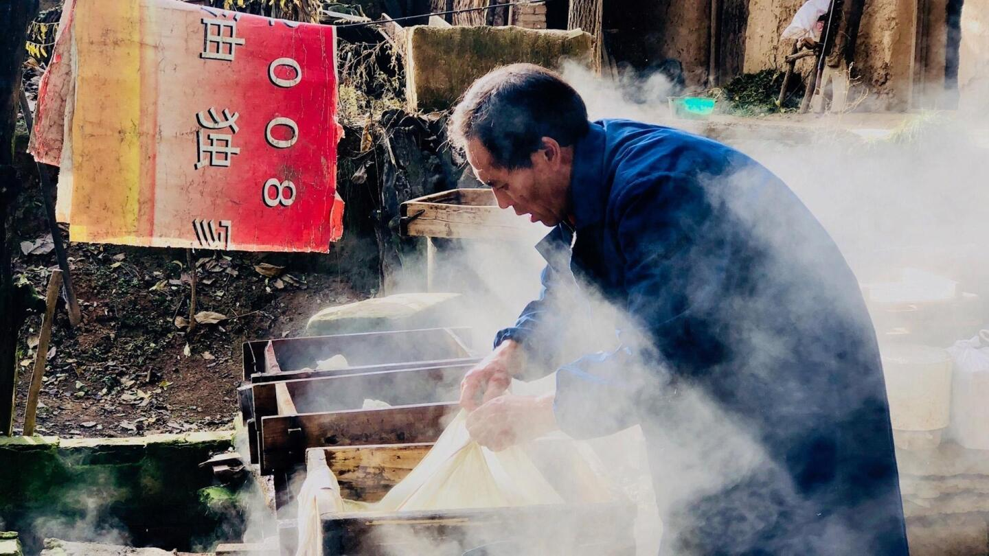 "A man pulls on a sheet-like substance while engulfed in smoke. | ""Voices from the Frontline: China's War on Poverty"""