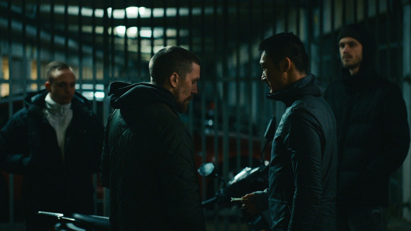 "An exchange between two men in the dark. | Still from ""Follow the Money"" Season 3, Episode 2"