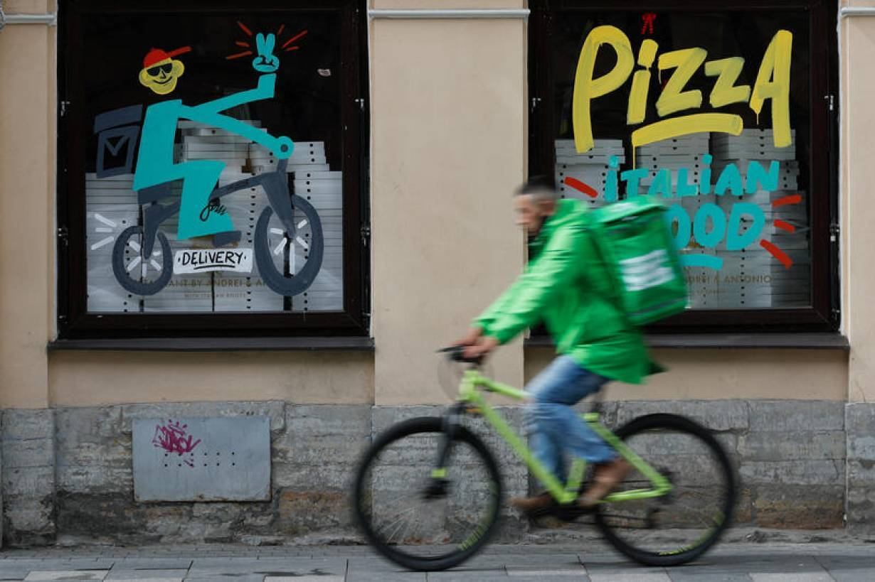 FILE PHOTO: A delivery person rides a bicycle past a restaurant, amid the outbreak of the coronavirus disease (COVID-19) in Saint Petersburg, Russia June 5, 2020.