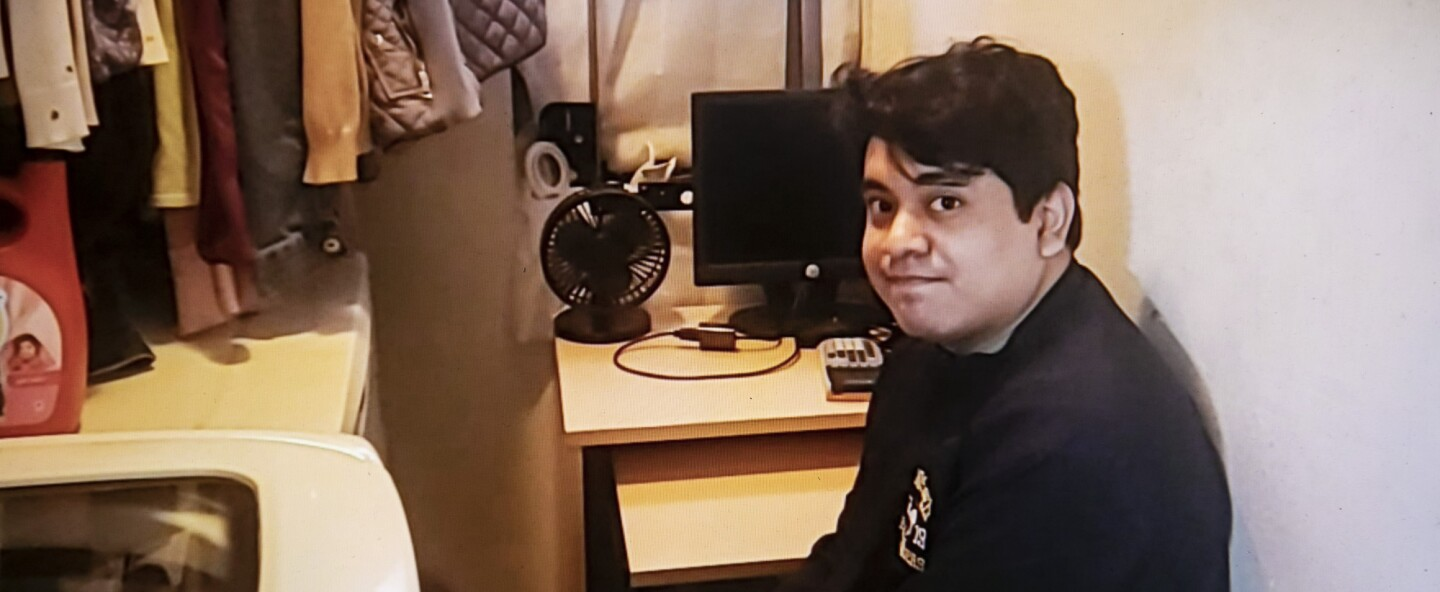 A young man raises his eyebrows at the camera as he sits at a cramped desk next to a washing machine and clothes hanging on a rack.