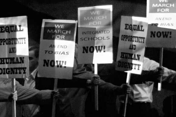 """Demonstrators wave signs during a civil rights protest in """"pool '63."""""""