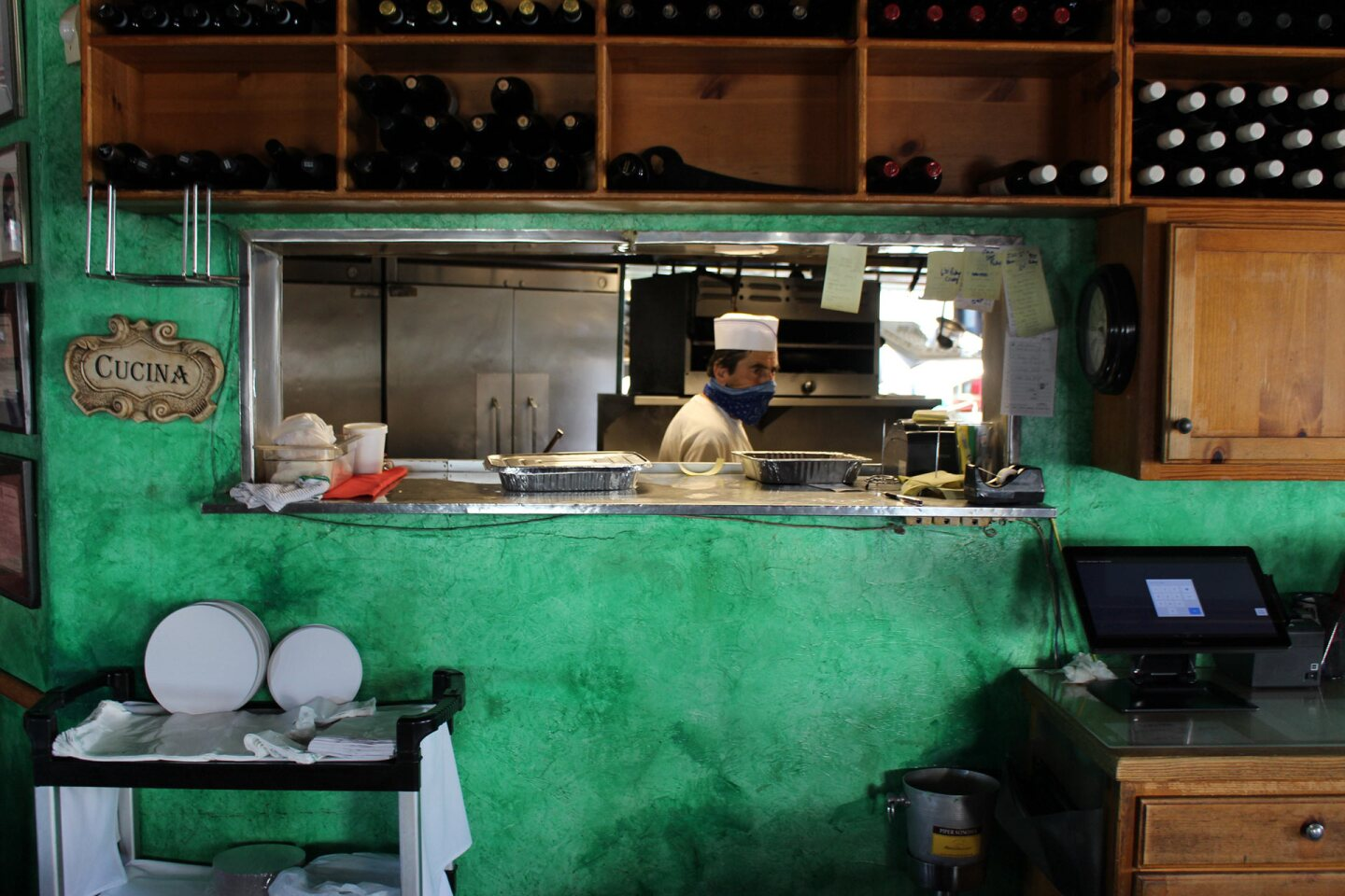 A cook in a mask stands in the kitchen ofCantalini's restaurant in Playa del Rey.   Karen Foshay