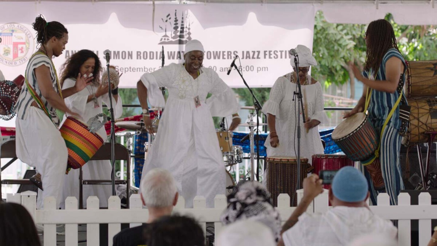 "A group of performers dance and drum at the Day of the Drum Festival at the Watts Towers Arts Center. | Still from ""Southland Sessions"" "" Watts Towers Festivals"""