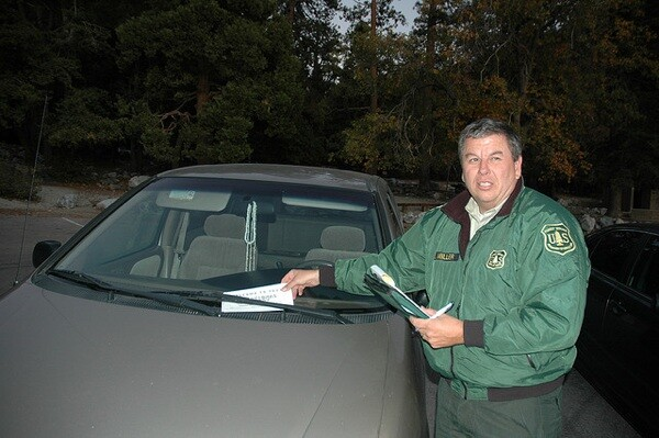 John Miller issues a ticket for parking in the San Bernardino National Forest without a day or adventure pass | Photo: John Heil/USFS