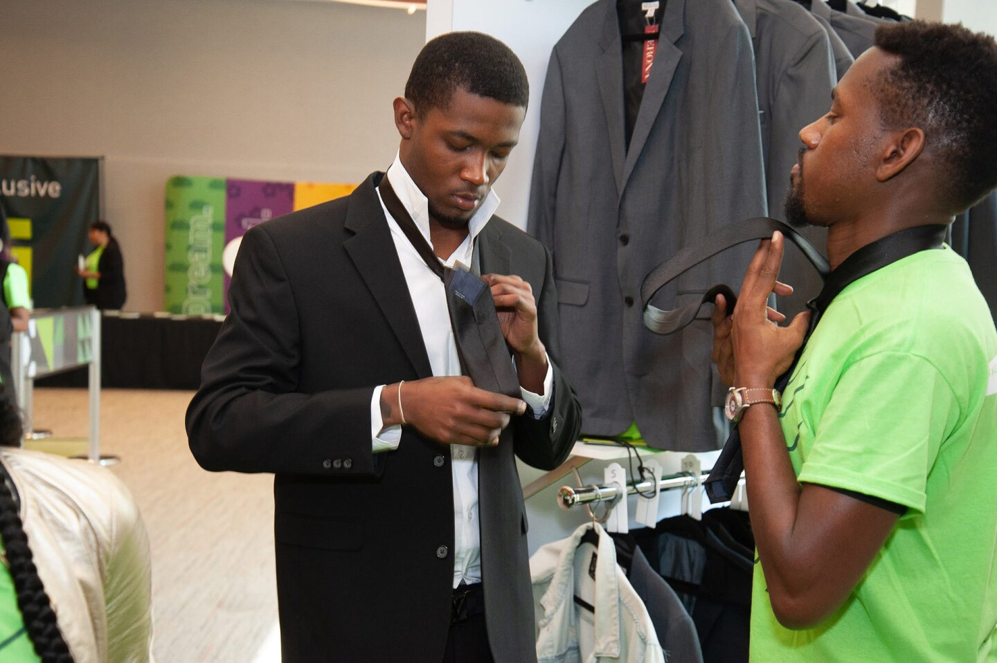 A young man teaches another young man how to tie a tie. | Courtesy of LeadersUp