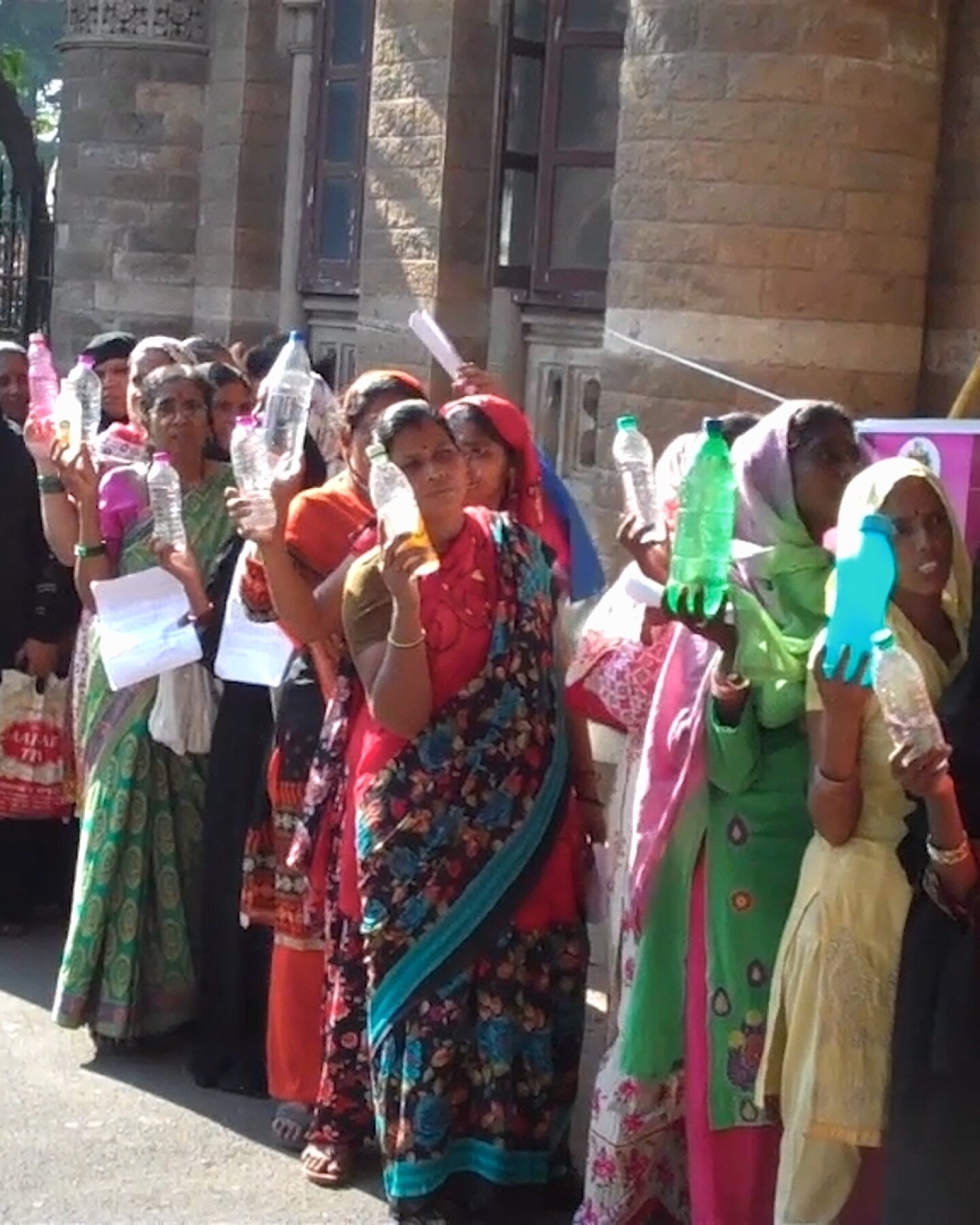 """Women in Mumbai line up to present local government officials examples of bad drinking water from their homes.   Still from """"Global Mosaic"""""""