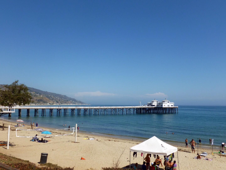 Malibu Pier visitors walk around the beach sand.