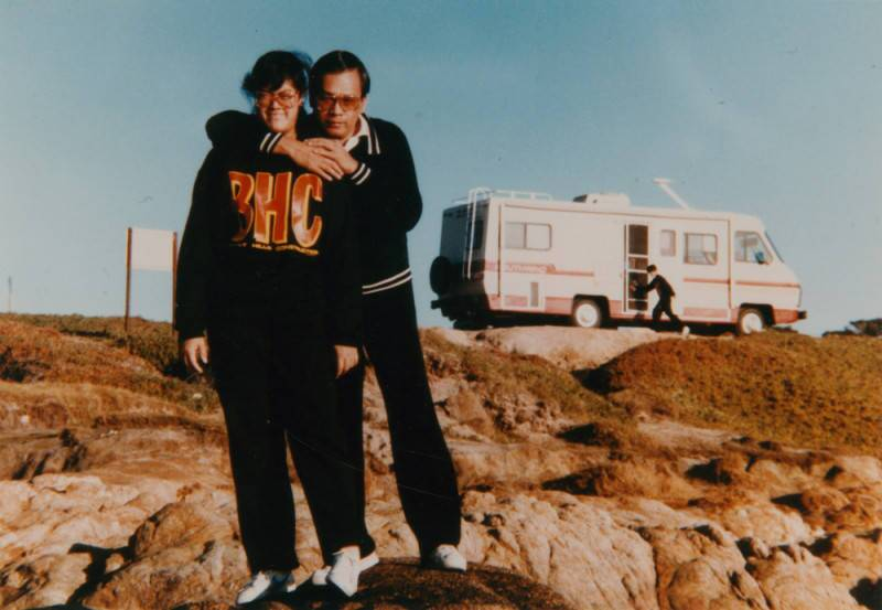 A girl and her father stand in front of an RV together