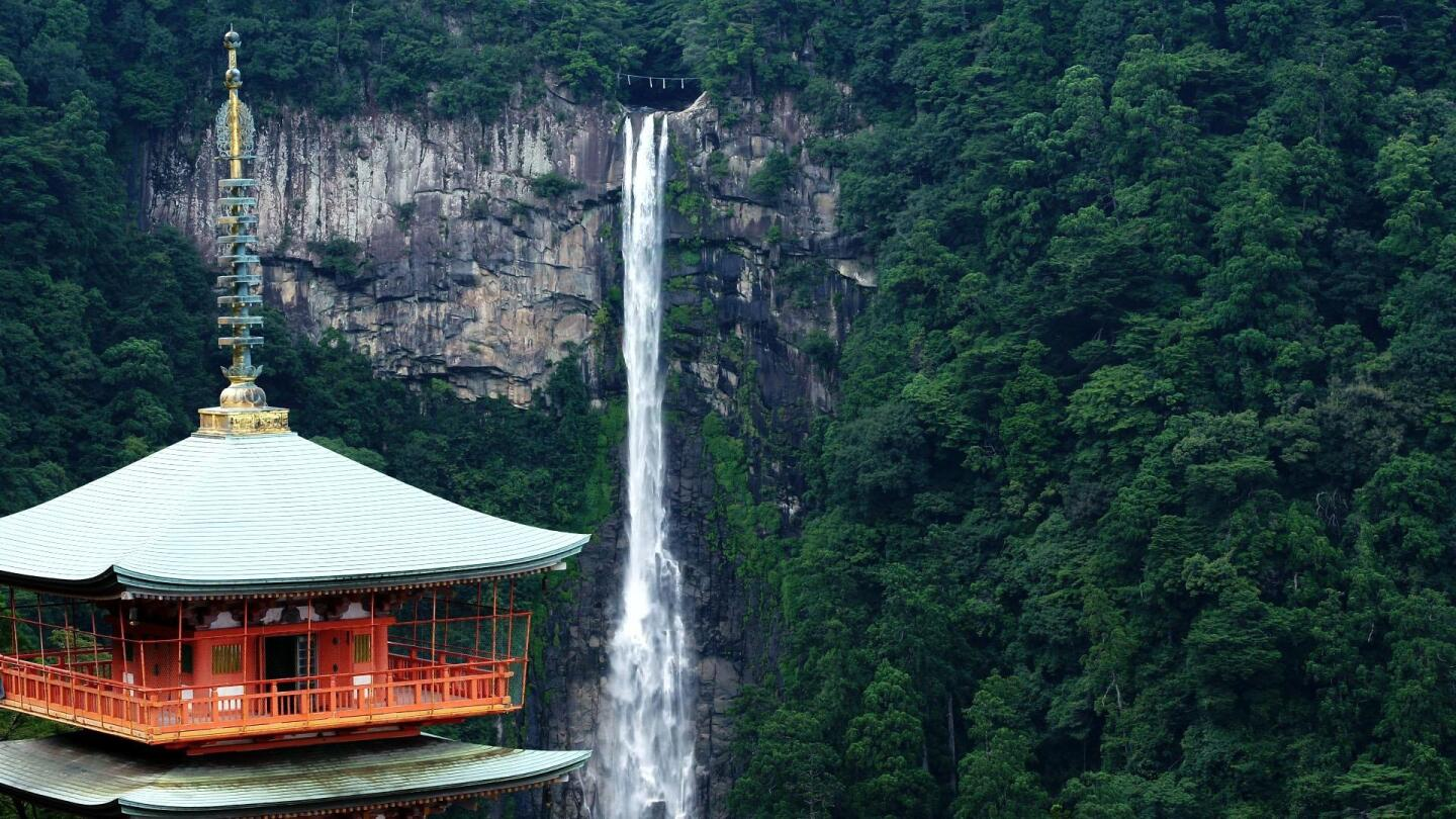 """A landscape of a waterfall and Japanese temple. 