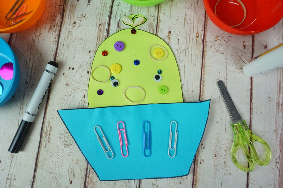 A green and blue paper cutout shaped like a cupcake decorated with google eyes, sequins, paper clips and rubber bands.