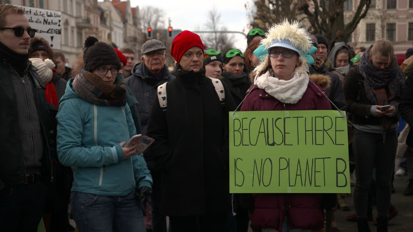 """German protesters against the coal industry gather on a street and one person's sign reads, """"Because There Is No Planet B."""""""
