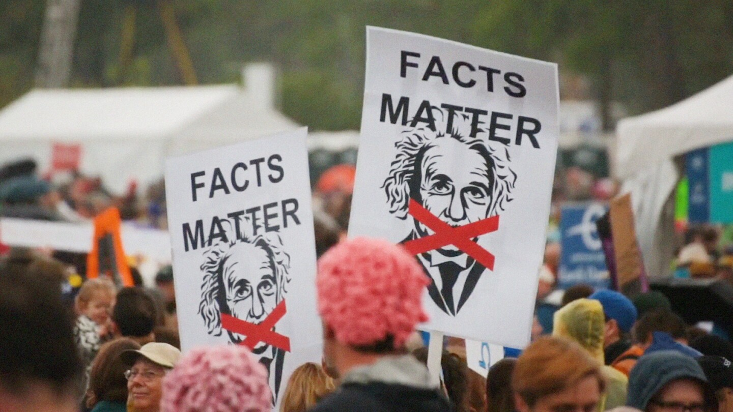 """Protesters hold up signs depicting Albert Einstein and an """"X"""" across his mouth, with the words """"Facts Matter."""""""