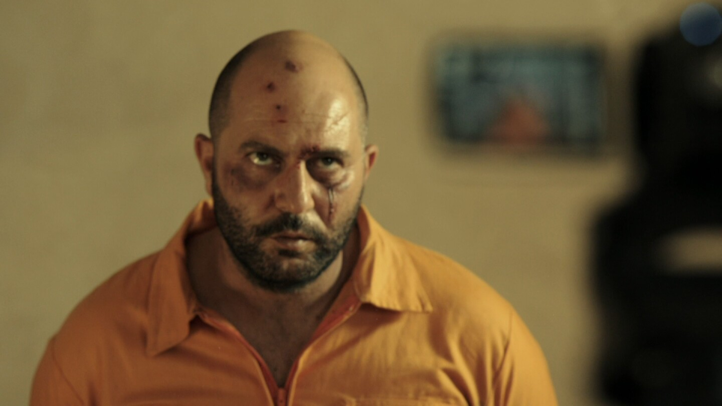 """A bloodied man stares intensely at something. 