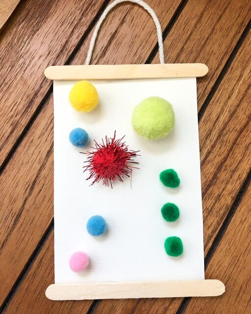 A hanging craft made out of popsicle sticks and colorful pom poms pasted onto a piece of paper with a string on top of it as a handle.