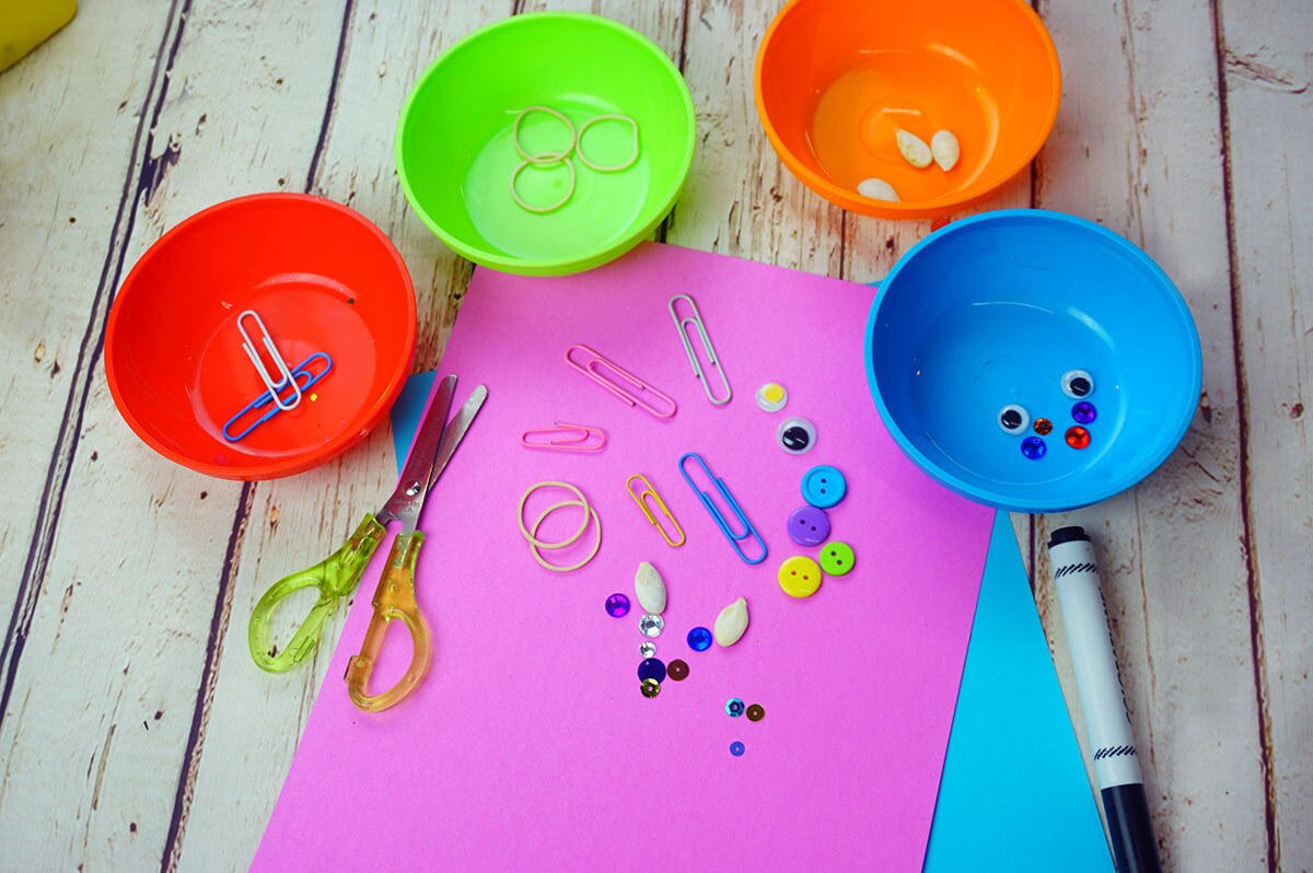 A piece of pink paper covered in small objects including sequins, paper clips and more surrounded by 4 colorful bowls filled with more of each of the items.