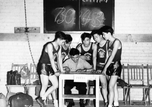 Chinese members of the Cathay basketball club gathered around Louie Lee, scorekeeper. They are playing the Wah Kue basketball team. | Harry Quillen Collection, Los Angeles Public Library